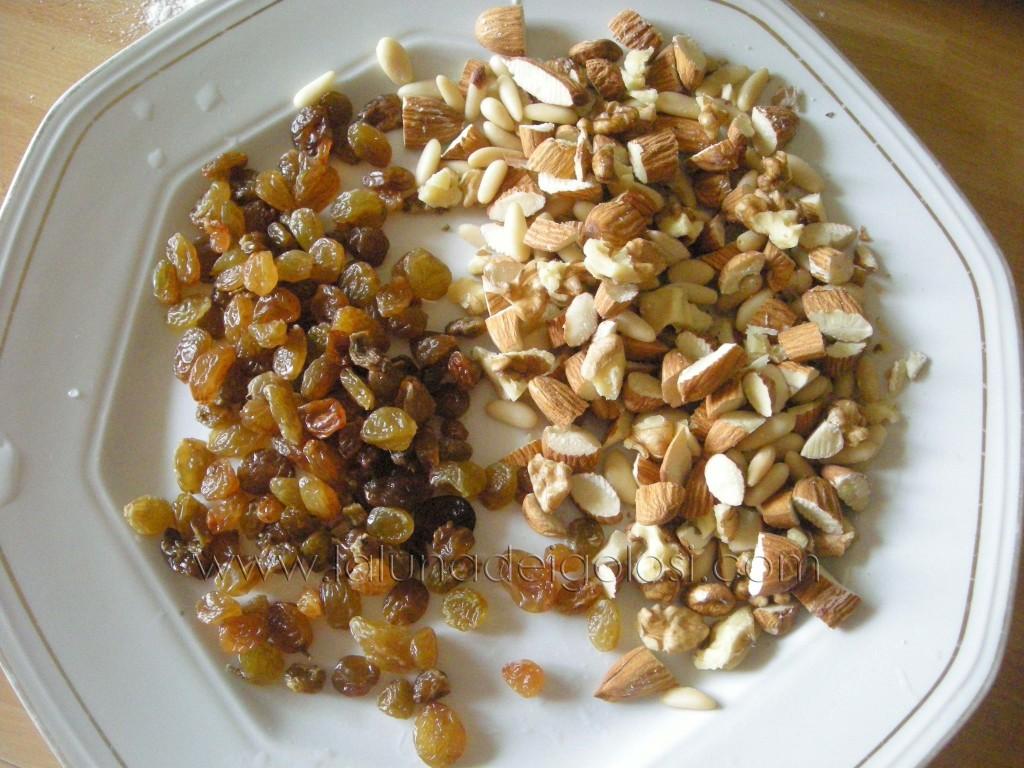 trita grossolanamente mandorle e noci e fai rinvenire l'uvetta in acqua bollente