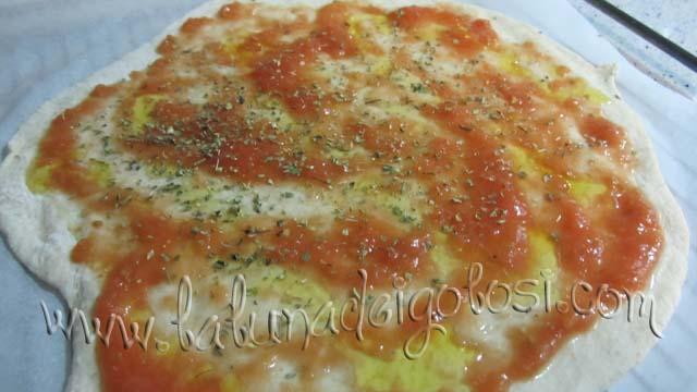 Condisci con qualche cucchiaiata di salsa di pomodoro, con il prosciutto cotto, l'olio, il sale e l'origano