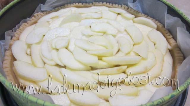 Ricopri quindi il disco di pasta con le fettine di mele disposte a raggiera e zuccherale con qualche cucchiaio di zucchero