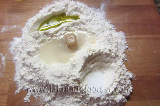 metti la farina sul tagliere, aggiungi il lievito, lo zucchero, l'olio e da una parte il sale