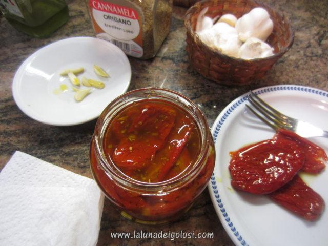 metti i pomodori nel vasetto, versa l'olio , aggiungi aglio e peperoncino tritati