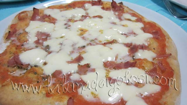 Poi apri il forno, metti sulla pizza la mozzarella, lasciala altri 3-4' nel forno