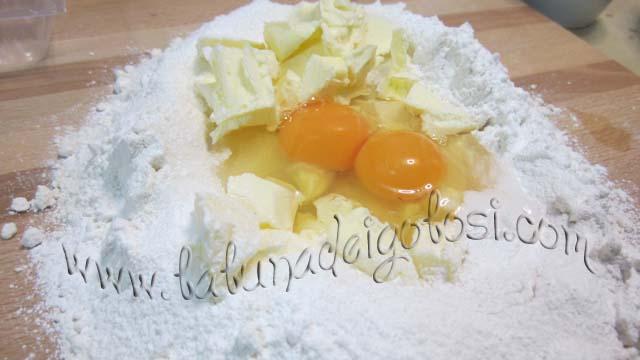Setaccia la farina a fontana sul tavolo, aggiungi lo zucchero, nel centro metti il burro FREDDO, le uova intere, il pizzico di sale e il lievito setacciato, poi amalgama il tutto velocemente.