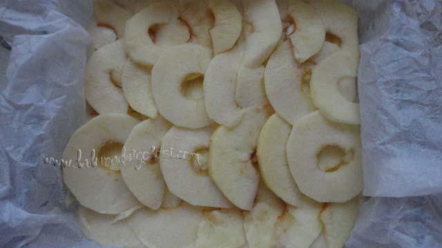 Taglia a spicchi molto sottili le due mele e mettile sulla torta