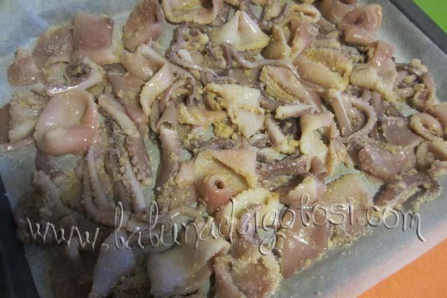 Versate i pezzettoni di calamaro in una teglia foderata con carta forno, sistemateli in modo che non si sovrappongano